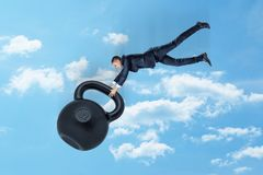 A young businessman in mid air gripping hold of a disproportionately big kettlebell with number 32 on it. royalty free stock photography