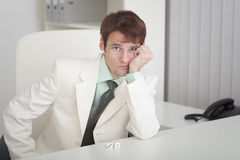 Young businessman misses on workplace at office Royalty Free Stock Images