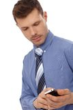 Young businessman with mobile phone. Young businessman in blue shirt using mobilephone Royalty Free Stock Photos