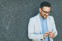 Young businessman with mobile phone by the grey wall. Handsome young businessman with mobile phone by the grey wall Royalty Free Stock Photos