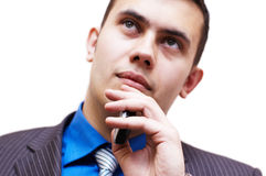 Young businessman with mobile phone thinks. Young businessman with mobile phone thinking about his work Royalty Free Stock Image