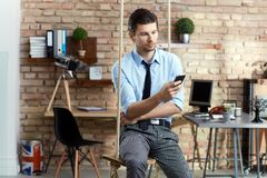 Young businessman with mobilephone. Young businessman sitting on swing, using mobilephone in modern office Royalty Free Stock Photography