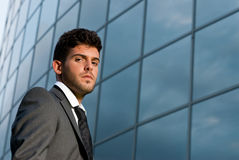 Young businessman on modern building background Stock Image
