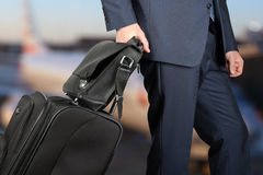 Young businessman  in  a modern  stylish suit with  luggage in. The young businessman  in  a modern  stylish suit with  luggage in  the airport Royalty Free Stock Images