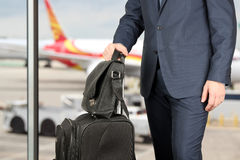 Young businessman  in  a modern  stylish suit with  luggage in  the airport Stock Photography