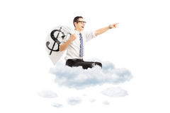 Young businessman with a money bag with dollar sign flying on cl Royalty Free Stock Images