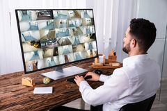 Businessman Monitoring CCTV Camera Footage On Computer. Young Businessman Monitoring CCTV Camera Footage On Computer Over Wooden Desk royalty free stock photos