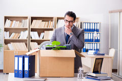 The young businessman moving offices after being made redundant. Young businessman moving offices after being made redundant Stock Images