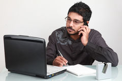 Young businessman multitasking Royalty Free Stock Photography
