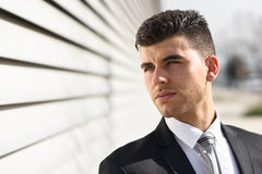 Young businessman near a office building wearing black suit Stock Images