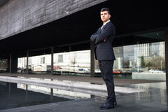 Young businessman near a office building wearing black suit Royalty Free Stock Image