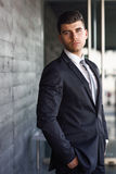 Young businessman near a office building wearing black suit Stock Photography