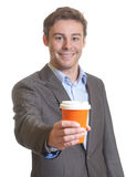 Young businessman offers a cup of coffee Royalty Free Stock Photo