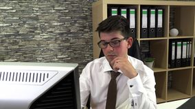Young businessman in the office. He is on the computer. Technology stock footage