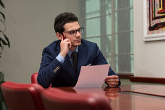 Young Businessman In Office Looking At Paper Royalty Free Stock Photo
