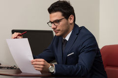 Young Businessman In Office Looking At Paper Royalty Free Stock Photography