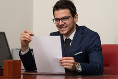Young Businessman In Office Looking At Paper Stock Photos