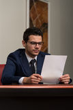 Young Businessman In Office Looking At Paper Stock Image