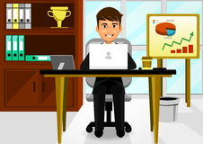 Young Businessman In The Office. A young businessman in the office using a laptop Stock Photo