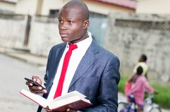 Young businessman with a book and a portable phone. royalty free stock photography