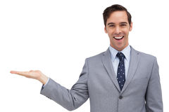 Young businessman with open hand looking at the camera Stock Image
