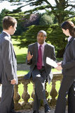 Young businessman outdoors in conversation with colleagues Royalty Free Stock Images