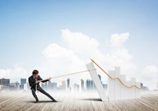 Man pulling with effort big pulling rope graph, as a symbol of financial growth. Young businessman outdoors making huge graph move Royalty Free Stock Photography