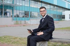 Young businessman outdoors. Young businessman in suit against modern building Royalty Free Stock Photos