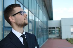 Young businessman outdoors. Young businessman in suit against modern building Royalty Free Stock Image
