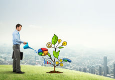 Young businessman outdoors watering drawn growth concept with can Stock Image
