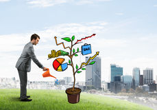 Young businessman outdoors watering drawn growth concept with can Stock Photography