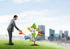 Young businessman outdoors watering drawn growth concept with can Royalty Free Stock Photo