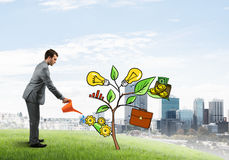 Young businessman outdoors watering drawn growth concept with can Stock Photos