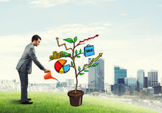Young businessman outdoors watering drawn growth concept with can Royalty Free Stock Photography