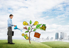 Young businessman outdoors watering drawn growth concept with can. Handsome businessman presenting investment and financial growth concept Stock Images