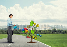 Young businessman outdoors watering drawn growth concept with can Stock Photo
