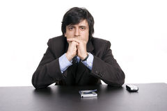 Young Businessman over a desk, full of thoughts Royalty Free Stock Photo