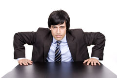 Young Businessman over a desk, full of thoughts Royalty Free Stock Images