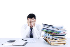 Young businessman overwhelmed. With stack of files on the desk Stock Photo