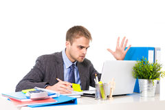 Young businessman overworked looking worried sitting at office computer desk in stress Stock Image