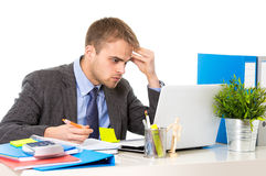 Young businessman overworked looking worried sitting at office computer desk in stress. Young desperate businessman overworked and upset looking worried and Royalty Free Stock Photos