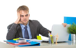 Young businessman overworked looking worried sitting at office computer desk in stress Stock Photo