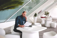 Young businessman with paper documents and open net-book decides important issues via cell telephone while sitting in office inter Stock Photography