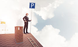 Young businessman with parking sign standing on brick roof. Mixe Stock Photos
