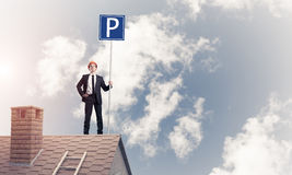 Young businessman with parking sign standing on brick roof. Mixe Royalty Free Stock Images
