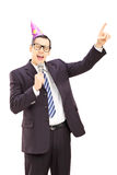 Young businessman with party hat singing on microphone Stock Photography