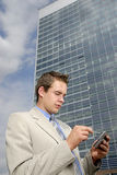 Young businessman with PDA. In his hands in front of business building Stock Image
