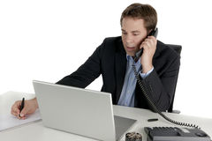 Young businessman at the phone. A Young businessman at the phone making notes with his pen Stock Image
