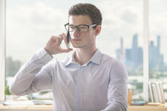Young businessman on phone. Closeup portrait of attractive young man talking on mobile phone in room with various items on windowsill and city view Royalty Free Stock Image