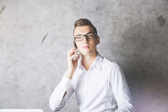 Young businessman on phone. Portrait of handsome young businessman on the phone. Concrete background. Communication concept Stock Image